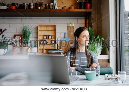 Fiducioso, premurosa donna che lavorano al computer portatile, a guardare fuori dalla finestra nel cafe Immagini Stock