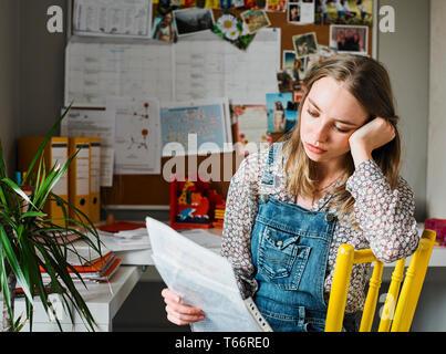 Focalizzato giovane donna che lavorano in ufficio in casa la lettura di documenti cartacei Immagini Stock