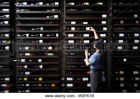 Sommelier femmina raggiungendo per la bottiglia di vino sulla cremagliera Immagini Stock