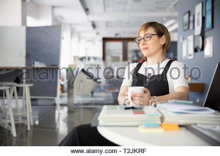 Riflessivo imprenditrice godendo la pausa caffè in ufficio Immagini Stock