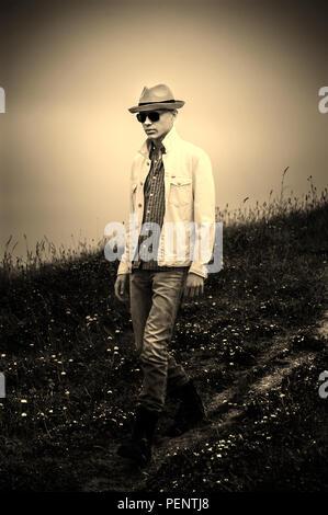 Giovane uomo che indossa hat a piedi nella natura Immagini Stock