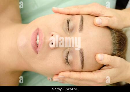 Giovane donna su spa trattamenti di massaggi in beauty spa salone. Cosmetologo rendendo ragazza rilassante massaggio viso e testa. Estetista medico. Spa la pelle e bo Immagini Stock