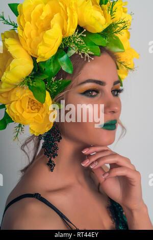 Ritratto di una splendida bionda con brillante trucco e un cerchio di fiori di colore giallo Immagini Stock