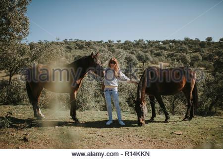 Una donna in piedi tra due cavalli in un campo Immagini Stock