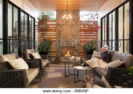 Senior donna rilassarsi leggendo un libro sul divano accanto al caminetto Immagini Stock