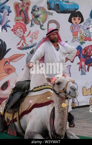 Un uomo vestito in arabo tradizionale indumento stand con un cammello nel Parco Tsvetochny nel centro di Grozny capitale della Cecenia ufficialmente la Repubblica cecena nel Nord Caucaso Distretto federale della Russia. Immagini Stock