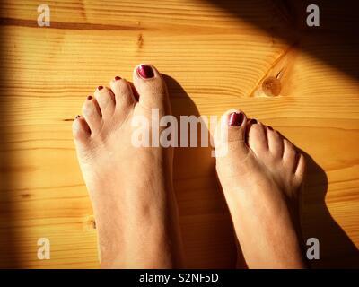I piedi femminili con chiodi rossi Immagini Stock