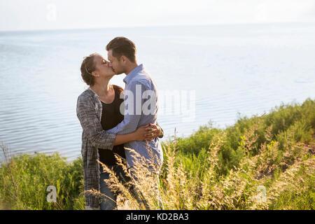 L uomo e la donna baciare dal mare Immagini Stock