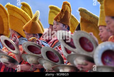 Xigaze, la Cina della regione autonoma del Tibet. 17 Luglio, 2019. I monaci frequentare un display Thangka rituale al monastero di Tashilhunpo in Xigaze, a sud-ovest della Cina di regione autonoma del Tibet, 17 luglio 2019. Thangka sono Buddista Tibetana opere dipinte su cotone o seta. I dipinti di soggetto religioso può essere fatta risalire al X secolo e tipicamente rappresentano Divinità buddiste. Credito: Chogo/Xinhua/Alamy Live News Immagini Stock