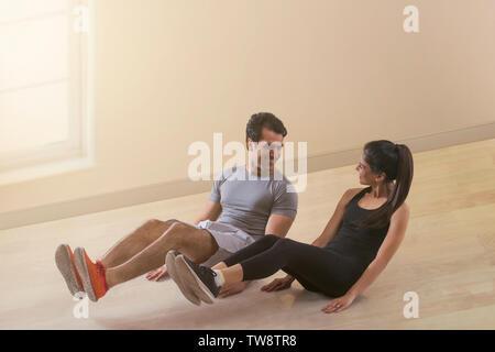 Coppia giovane facendo esercizio sul pavimento Immagini Stock