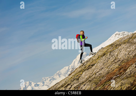 Un runner corre su una ripida montagna roccia ad alta altitudine. Immagini Stock