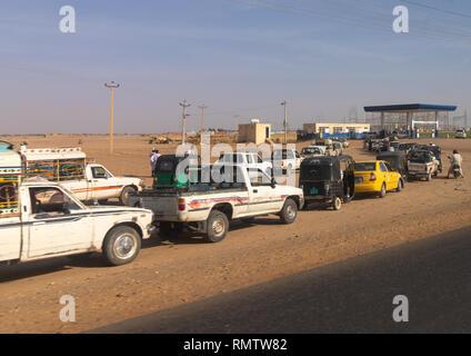 Popolo sudanese nella loro coda di automobili sulla linea in corrispondenza di una stazione di gas durante la penuria di carburante, stato settentrionale, Meroe, Sudan Immagini Stock