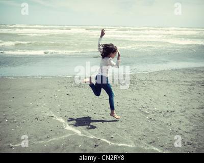 Ragazzina salta alla spiaggia. Immagini Stock