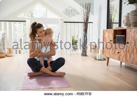 Affettuosa madre holding baby figlia sul materassino yoga Immagini Stock