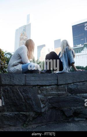 Due giovani donne sedute in Central Park in autunno Immagini Stock