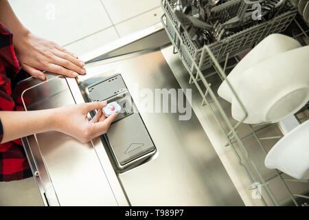 Donna mette la compressa in lavastoviglie. Immagini Stock