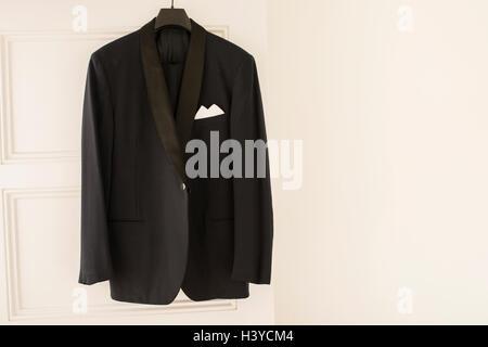 Cena nero giacca appeso sulla porta appendiabiti in vuoto in camera bianca. Parete con copia spazio. Immagini Stock
