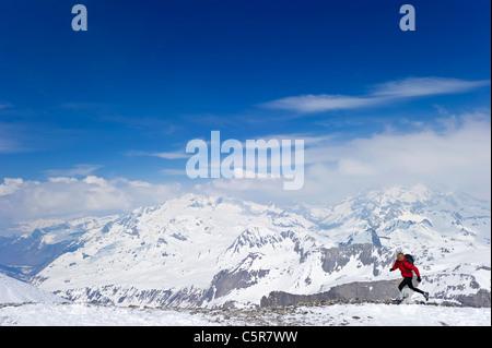 Una donna in esecuzione in alta montagna cime innevate. Immagini Stock