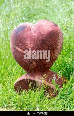 In legno intagliato cuore a Daylesford fattoria organica summer festival. Daylesford, Cotswolds, Gloucestershire, Inghilterra Immagini Stock