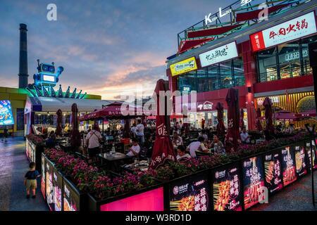 Urumqi, della Cina di Xinjiang Uygur Regione autonoma. 14 Luglio, 2019. La gente visita un ristorante zona sulla strada di Urumqi, a nord-ovest della Cina di Xinjiang Uygur Regione autonoma, luglio 14, 2019. Notte-economia di tempo è stato il prelievo in Urumqi a partire dal mese di luglio. Le persone si divertono a raffreddare le notti estive da shopping e degustazione del cibo. Credito: Zhao Ge/Xinhua/Alamy Live News Immagini Stock