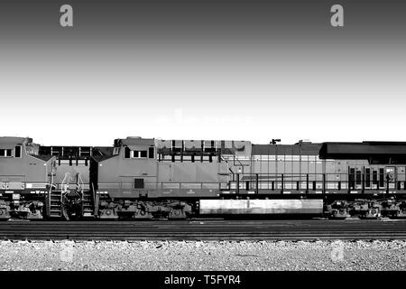 Un General Electric Dash 9 stand con carichi su un treno cantiere nel deserto in aghi. Immagini Stock
