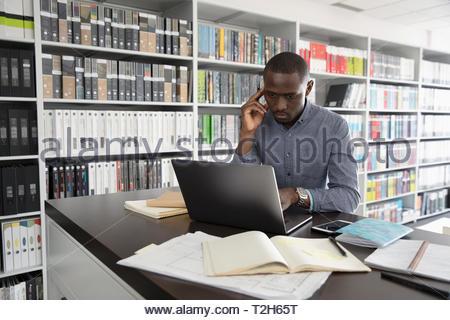 Maschio focalizzato interior designer che lavora al computer portatile in design studio Immagini Stock