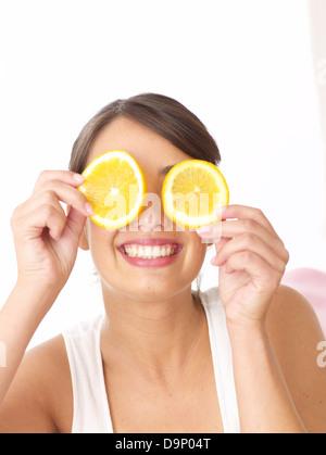 Donna che mantiene le fette di colore arancione nella parte anteriore del suo viso Immagini Stock