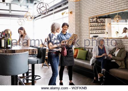 Cameriera mostra menu per donna in ristorante Immagini Stock