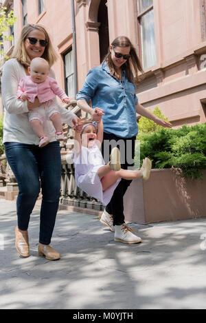 Le madri caucasica figlia oscillante sul marciapiede della città Immagini Stock