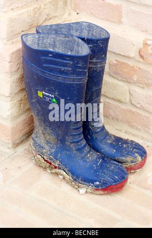 Fango incrostato blu stivali wellington ordinatamente stimolato contro un muro di mattoni Immagini Stock