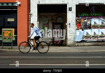 Una via dello shopping nel centro di Berlino, un ciclista passa attraverso una porta che è coperto di graffiti e poster. Immagini Stock