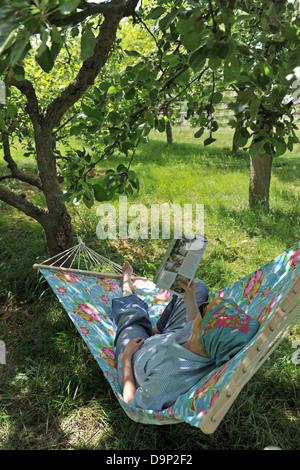 Donna sdraiata in amaca rivista di lettura Immagini Stock