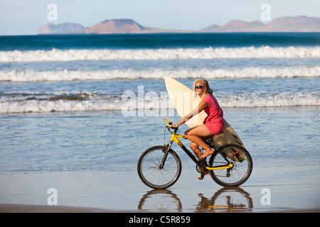 Surfer equitazione mountain bike lungo gli oceani edge. Immagini Stock