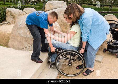 Ragazzo aiutare la sua zia di sollevare la sua madre fino a passo nel parco. Signor © Myrleen Pearson ...Ferguson Cate. Serie di 4 immagini Immagini Stock