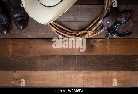 Cowboy americano elementi inclusa un lazo speroni e un tradizionale cappello di paglia su un asse di legno sfondo Immagini Stock