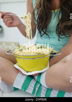 Giovane donna seduta sul banco di cucina mangiare spaghetti Immagini Stock