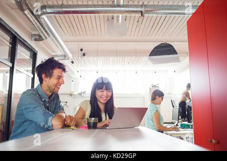 Uomo e due donne che lavorano in ufficio, donna in piedi da una finestra in background Immagini Stock