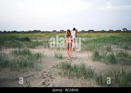 Madre e figlia camminando sulla duna di sabbia Immagini Stock
