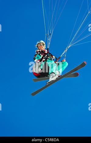 Una femmina di pilota di parapendio sorrisi mentre battenti passato. Immagini Stock