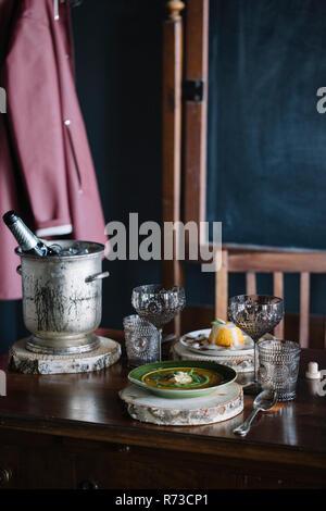 Ciotola di fresco guarnita di zuppa, un dessert e champagne sulla tavola vintage Immagini Stock