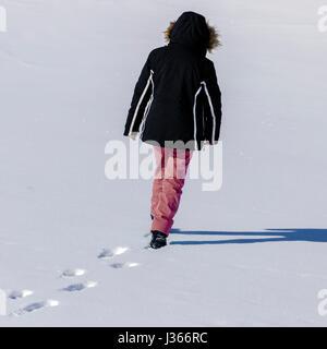 Una donna a piedi nella neve profonda Immagini Stock