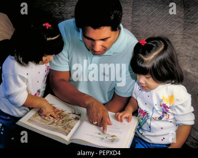 Eredità messicana papà lettura storybook insieme con figlie gemelle sorelle. Signor © Myrleen Pearson ...Ferguson Cate Immagini Stock