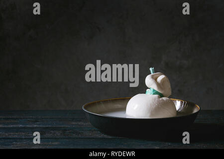 Ciotola con tutta legata al formaggio italiano burrata in salamoia su tavola in legno tavolo. Scuro in stile rustico Immagini Stock