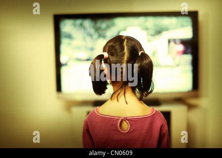 Orologi ragazza sullo schermo del televisore. Immagini Stock