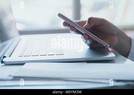 Mano di African American donna sms sul cellulare Immagini Stock