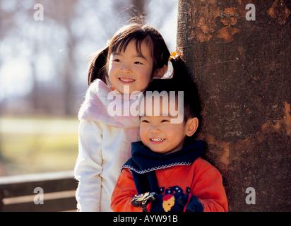 Ragazza con suo fratello in piedi da una struttura ad albero Immagini Stock