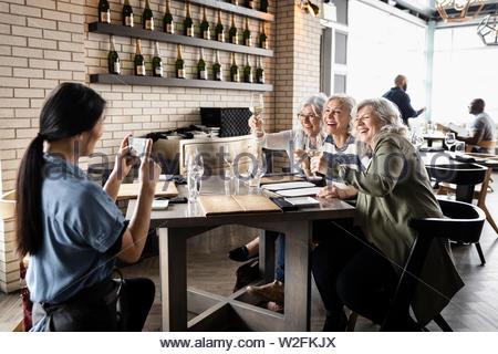 Cameriera di fotografare felici donne gli amici a bere vino bianco nel wine bar Immagini Stock