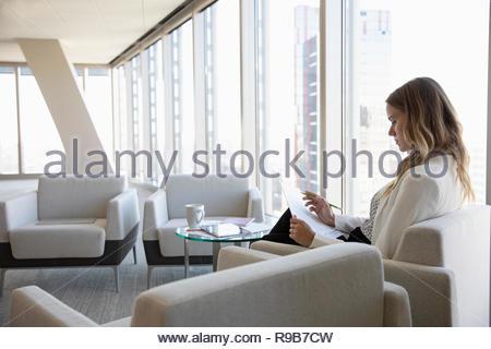 Imprenditrice la revisione dei documenti in office lounge Immagini Stock