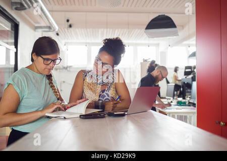 Le donne che lavorano da tavolo in ufficio, i colleghi di lavoro in background Immagini Stock