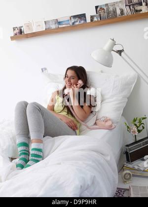 Bruna giovane donna al telefono nel letto Immagini Stock